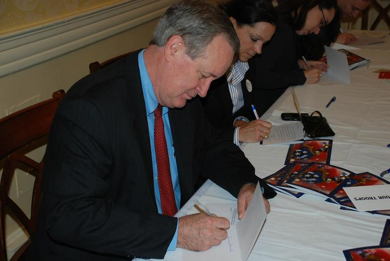 Senator Crapo signs Christmas cards for our troops serving overseas at a Red Cross Holiday Mail for Heroes event.